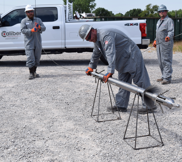 Caliber team members work with wireline logging equipment