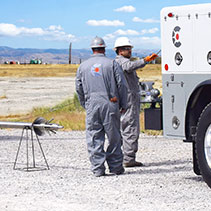 Caliber team members with a wireline truck and wireline logging equipment